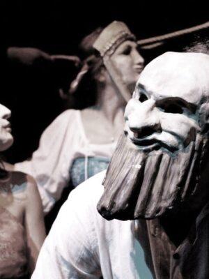 Fotografia przedstawia trzy osoby w greckich maskach, w bliskich ujęciu. Na pierwszym planie, po prawej stronie, stoi mężczyzna w białej koszuli, spoglądający w lewo. Na twarzy ma białą maskę przedstawiającą brodate oblicze z baranimi rogami. Po lewej stronie stoi zwrócona do obiektywu profilem młoda kobieta z jasnymi włosami; spogląda w prawo. W tle pomiędzy nimi, nieco z tyłu, stoi kolejna kobieta w masce, także spoglądająca w prawo.