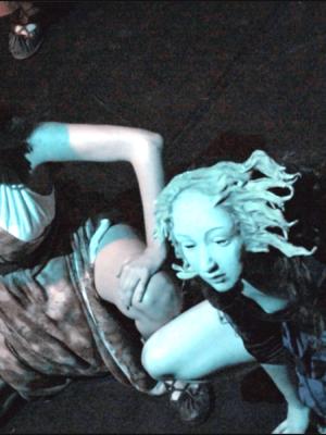 Ujęcie przedstawia widziane z góry, pod dużym kątem, dwie kobiety w białych, greckich maskach, kucające na ciemnej podłodze. Obie kierują wzrok w lewo i w dal, poza kadr. Kobieta po prawej stronie ma na sobie ciemną bluzkę i spódnice w pasy, ręce trzyma oparte na podłodze. Kobieta z lewej, ubrana w jasnobrązową suknię bez rękawów, opiera dłonie na udach.