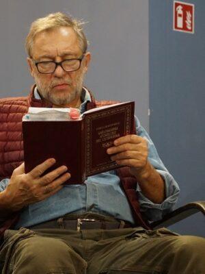 """Na fotelu, na tle niebieskiej ściany, siedzi starszy mężczyzna z siwiejąca broda, w okularach, który w skupieniu czyta książkę – zbiorcze wydanie """"Warszawianki"""", """"Wyzwolenia"""" i """"Nocy listopadowej"""" Stanisława Wyspiańskiego, o czym informują litery widoczne na okładce. Mężczyzna ma na sobie zielone spodnie, jasnoniebieską koszulę i czerwoną kamizelkę."""