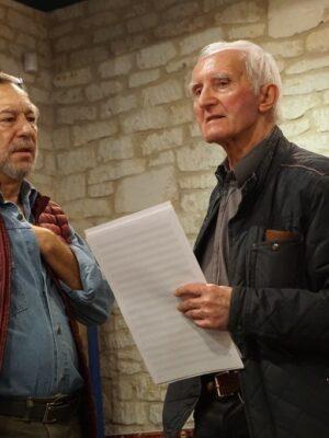 Fotografia przedstawia dwóch mężczyzn ujętych od pasa w górę na tle ściany z białego kamienia. Mężczyzna po lewej stronie, ubrany w jasnoniebieską koszulę i czerwona kamizelkę, ma siwiejąca brodę i wykonuje rękami gesty na wysokości piersi. Obok niego, po prawej stronie, stoi starszy mężczyzna w ciemnej kurtce, z krótkimi, całkiem białymi włosami, który spogląda przed siebie. W lewej ręce trzyma plik zapisów nutowych.