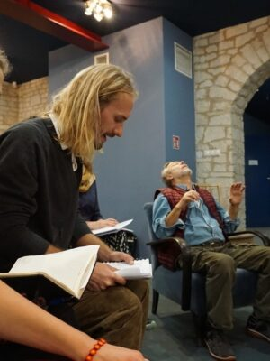 Fotografia przedstawia cztery osoby w sali o ścianach z białego kamienia i niebieskich sufitach. Na pierwszym planie, po lewej stronie, siedzą młody mężczyzna i młoda kobieta, którzy nachylają się nad zeszytami. Za nimi, przy środku siedzi w fotelu starszy mężczyzna w zielonych spodniach, niebieskiej koszuli i czerwonej kamizelce, który unosi ręce na wysokość swojej piersi i odchyla głowę do tyłu. Obok niego, po prawej stronie, stoi mężczyzna w ciemnej koszuli w pionowe pasy i w okularach, który gra na skrzypcach.