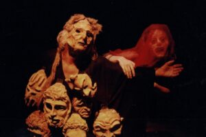 Ekspresyjne ujęcie dwóch widmowych postaci na czarnym tle, ujętych od pasa w górę. Na pierwszym planie, nieco z lewej, zamaskowany mężczyzna w czarnej szacie rozkłada szeroko ręce. Do jego szaty, na korpusie, przyczepionych jest siedem masek nawiązujących do stylistyki starożytnej Grecji. Za nim wyłania się twarz kobiet w masce wyobrażającej przerażenie. Kobieta opiera dłoń na wyciągniętym ramieniu mężczyzny.