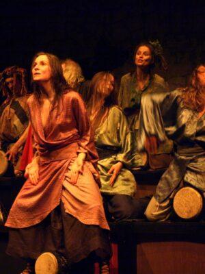 Fotografia przedstawia grupę siedmiu kobiet i dwóch mężczyzn na ciemnym tle, siedzących na drewnianych podwyższeniach i grających ekstatycznie na trzymanych między nogami bębnach. Wszyscy ubrani się w kostiumy nawiązujące do stylistyki japońskich kimon i starożytnych szat greckich. Kobieta w środku, najbardziej z przodu, jako jedyna nie gra na bębnie, lecz stoi i spogląda w lewo i w górę, poza krawędź kadru.