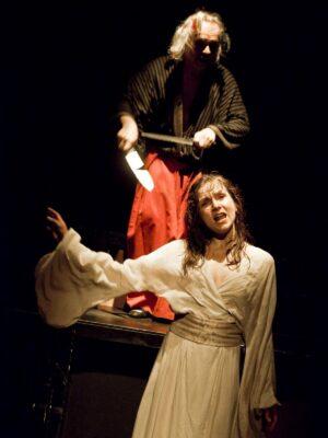 Ekspresyjna fotografia przedstawiająca, na czarnym tle, młodą kobietę w prostej, białej sukni i stojącego za nią na wysokim, drewnianym podeście starszego mężczyzną z półdługimi, siwymi włosami i brodą. Kobieta śpiewa, prawą rękę wyciąga w stronę lewej krawędzi kadru Mężczyzna ma na sobie czarne kimono i szerokie, czerwone spodnie. Trzyma przed sobą, nad głową kobiety,dwa długie noże, w geście sugerującym, że ostrzy je o siebie nawzajem.