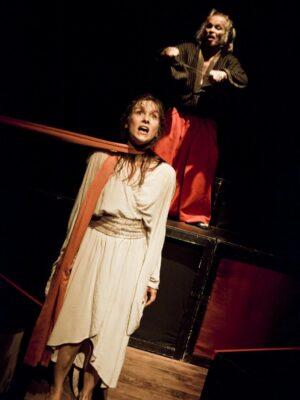 Ekspresyjna fotografia przedstawiająca, na czarnym tle, młoda kobietę w prostej, białej sukni i stojącego za nią na wysokim, drewnianym podeście starszego mężczyzną z siwymi włosami i broda. Kobieta stoi z opuszczonymi rękami, na szyi ma owiniętą szarfę, której jeden skraj ginie za lewą krawędzią kadru. Mężczyzna trzyma przed sobą, ponad jej głową, dwa długie noże, w geście sugerującym, że ostrzy je o siebie nawzajem.