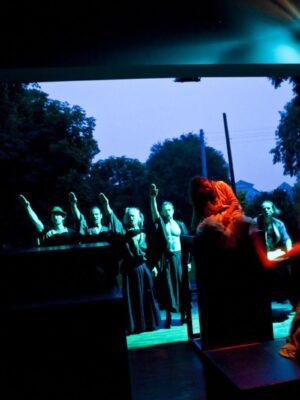 Ekspresyjna fotografia przedstawiająca słabo oświetloną, niewielką salę teatralną z szeroko otwartymi wrotami w ścianie, za którymi widać zarysy drzew i ciemniejące, wieczorne niebo. Na pierwszym planie, oświetlonym na pomarańczowo, elementy dekoracji w formie drewnianych prostopadłościanów. Na jednym z nich siedzi kobieta w białej sukni, przed nią siedzi na kolanach druga kobieta z uniesionymi do góry ramionami. W tle, w turkusowym świetle reflektora, rząd pięciu mężczyzn wyciągających do góry prawe ręce w geście pozdrowienia.