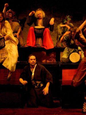 Ekspresyjna fotografia przedstawiająca grupę jedenastu grających na bębnach osób ubranych w stylizowane kostiumy nawiązujące do japońskich kimon i antycznych strojów greckich. Wszyscy usadowieni się na drewnianej dekoracji złożonej z trzech rzędów drewnianych pomostów. W centrum, u góry, siedzi siw, starszy mężczyzna z półdługimi włosami, w szerokich czerwonych spodniach. Bęben trzyma pomiędzy nogami. Po jego lewej i prawej stronie grający młodzi mężczyźni i kobiety. Jedna kobieta, w stroju łososiowej barwy, stoi na scenie przed pierwszym podestem i gra na bębnie trzymanym wysoko nad głową.
