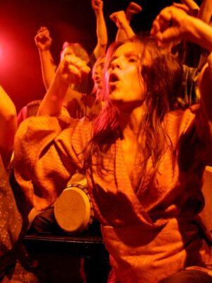 Ekspresyjna fotografia przedstawia bliskie ujęcie grupy skąpanych w pomarańczowym blasku młodych, skandujących kobiet. Kobiety, ubrane w kostiumy stylizowane na japońskie kimona i stroje greckie. Każda z nich trzyma pod pachą niewielki bęben, drugą rękę zaś wznosi z zaciśniętą pięścią do góry.