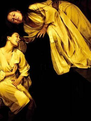 Stylizowana, ekspresyjna fotografia przedstawia dwie kobiety na czarnym tle, oświetlone mocnym, żółtym światłem, które nie wydobywa jednak z ciemności szczegółów dekoracji. Obie mają na sobie długie, białe suknie, nawiązujące trochę do estetyki japońskich kimon, a także do strojów antycznych. Kobieta po lewej stronie stoi w przyklęknięciu, jedną rękę opiera na łonie, drugie w pobliżu piersi i patrzy w lewo. Druga kobieta, nieco starsza, stoi na niewidocznym podwyższeniu i wychyla się na lewo, ponad pierwszą kobietą. Obie mają ciemne, długie włosy.