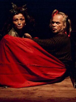 Fotografia przedstawia, w bliskim ujęciu i na ciemnym tle, starszego mężczyznę i młodą kobietę, siedzących bokiem do obiektywu na wyłożonej deskami podłodze pomiędzy dwoma drewnianymi prostopadłościanami, elementami dekoracji. Mężczyzna siedzi po prawej stronie, ma na sobie ciemną koszulę i czerwoną spódnicę, która zasłania jego wyciągnięte przed siebie nogi i ręce. Kobieta siedzi naprzeciwko niego, zasłonięta przez spódnicę mężczyzny. Widać tylko jej głowę, skierowaną twarzą w obiektyw i długie włosy, w które wpleciono liście.