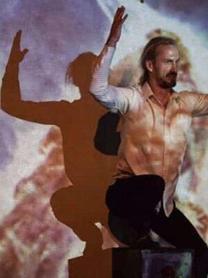 Fotografia przedstawia zwróconego nieco w prawo młodego mężczyznę o długich, jasnych włosach i brodzie, w białej koszuli, który wznosi ku górze ręce. Za nim, na ścianie, widać jego cień padający na wizualizację przedstawiającą kosmiczną mgławicę w pastelowych barwach, głównie fioletach i żółciach.