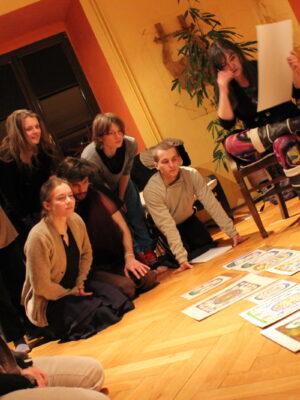 Zdjęcie, wykonane pod kątem czterdziestu pięciu stopni, przedstawia grupę osób klęczących i stojących na podłodze pomieszczenia w dawnej oficynie pałacowej i przyglądających się z uwagą rozłożonym na podłodze kolorowym pracom malarskim w formacie a4. Z lewej strony znajduje się grupa ośmiu młodych mężczyzn i kobiet. Większość z nich klęczy i nachyla się nad podłogą, by lepiej widzieć prace malarskie; dwie z nich stoją. Po prawej stronie, obok przykrytego białym obrusem stołu, siedzi na krześle ciemnowłosa kobieta w średnim wieku. Prawą nogę założyła na lewe kolano, w lewej ręce trzyma arkusz białego papieru, prawą wykonuje nieokreślony gest na wysokości swojej twarzy.