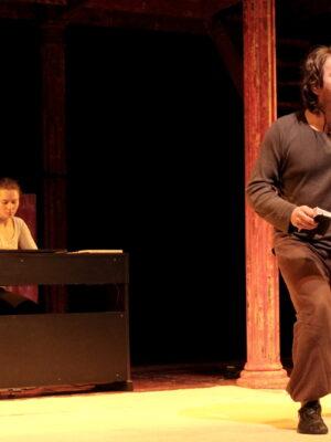 Na zdjęciu widać scenę w sali teatralnej. Scena jest niemal pusta, za wyjątkiem elementów dekoracji – pionowego, czerwonego słupa po prawej stronie, stojących obok drewnianych schodów, prostokątnej przegrody w tle, po lewej stronie, oraz podłużnego, czarnego pulpitu, także po lewej stronie, przy którym siedzi młoda dziewczyna w białej bluzce. Przed nią, na przodzie sceny, stoi młody mężczyzna w szarej bluzie, z półdługimi, ciemnymi włosami. W prawej ręce trzyma złożony notes. Lewą rękę wyciąga do nieco do góry. Palce tej dłoni są złożone, za wyjątkiem wyciągniętego lekko palca wskazującego.