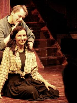 Na pierwszym planie dwójka młodych osób – jasnowłosy mężczyzna w szarej bluzie i ciemnowłosa kobieta w spódnicy – na scenie teatralnej. Za nimi, w tle, widać elementy dekoracji: drewniane schody i dwa pionowe słupy. Mężczyzna siedzi na krześle, a kobieta siedzi na podłodze, przed nim. Mężczyzna przygląda się zainteresowaniem wierzchołkowi jej głowy. Kobieta uśmiecha się do obiektywu.