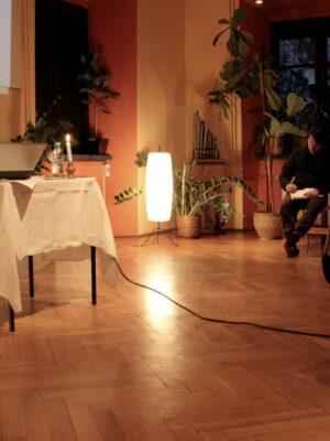 Wnętrze sali w dawnej oficynie pałacowej. Z lewej strony ustawiono niewielki stół i krzesło, na którym siedzi ciemnowłosy mężczyzna w średnim wieku. Za nim, na ścianie, wyświetlają się slajdy prezentacji uruchamianej z laptopa stojącego na stole. Z prawej strony, na krzesłach rozstawionych wzdłuż ściany i naprzeciwko stołu siedzi trójka młodych ludzi, dwóch młodych mężczyzn i młoda kobieta, którzy w skupieniu zapisują notatki w zeszytach. W kącie Sali stoi, w oszklonej gablocie, instrument przypominający małe organy. Obok stoi pionowa lampa podłogowa – jedyne źródło światła widoczne na fotografii.