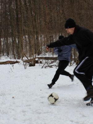 Fotografia przedstawia grupę pięciu osób we trakcie gry w piłkę nożną na przysypanej śniegiem leśnej polanie. Z lewej strony, z tyłu, stoi ubrany na czarno mężczyzna z siwą brodą, który podnosi ręce w geście gotowości na przyjęcie strzału. Z prawej strony biegnie grupa czterech osób, a jedna z nich – młody mężczyzna w czarnej czapce – szykuje się do kopnięcia piłki.