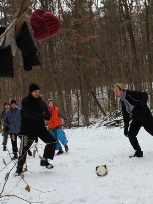 Na leśnej polanie, przysypanej śniegiem, grupa młodych mężczyzn i kobiet gra w piłkę nożną. Na pierwszym planie, na gałęzi, wiszą czerwona czapka i ciemna kurtka.