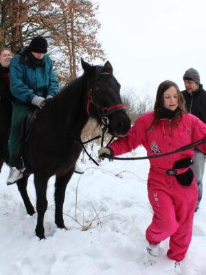 Na skraju lasu przysypanego śniegiem młoda kobieta w różowym kombinezonie prowadzi za uzdę czarnego konia, na którym siedzą młodzi mężczyzna i kobieta. Z prawej strony, za kobietą w różowym kombinezonie, stoi mężczyzna w ciemnej kurtce i w czapce, który przygląda się zwierzęciu.