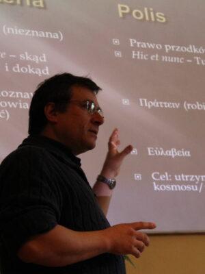 Fotografia przedstawia ujętego od pasa wzwyż ciemnowłosego mężczyznę w okularach, w średnim wieku, na tle ekranu, na którym wyświetlają się notatki dotyczące greckiej polis.
