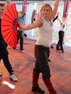 Fotografia przedstawia grupę młodych kobiet ćwiczących w sali treningowej układy taneczne z pomarańczowymi wachlarzami. Każda z nich trzyma duży wachlarz i naśladuje pozę kobiety prowadzącej zajęcia, stojącej z prawej strony, w ciemnej koszulce i czarnych spodniach z dwoma czerwonymi paskami.