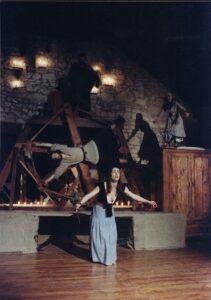 Na szarym podeście sześciokątna obrotowa konstrukcja z drewna, na której wisi, równolegle do podłoża, brodaty mężczyzna z rękami i nogami rozłożonymi na kształt litery X. Przed nim, na podłodze z desek stoi nachylona w lekkim ukłonie i z szeroko otwartymi ramionami młoda kobieta w niebieskiej spódnicy i czarnej kamizelce. Z prawej strony stoi drewniana szafa, na której stoi kobieta w szarej sukni. W tle, ponad drewnianą konstrukcją, stoi w półmroku mężczyzna na tle ściany z szarego kamienia.