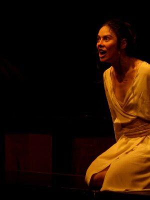 Ekspresyjna fotografia przedstawiająca na czarnym tle śpiewającą, młodą dziewczynę z ciemnymi włosami. Dziewczyna klęczy z prawej strony kadru, jest ujęta pod kątem; spogląda na wprost, w stronę lewej krawędzi zdjęcia. Ma na sobie prostą, jasną suknię, oświetloną żółtym światłem.