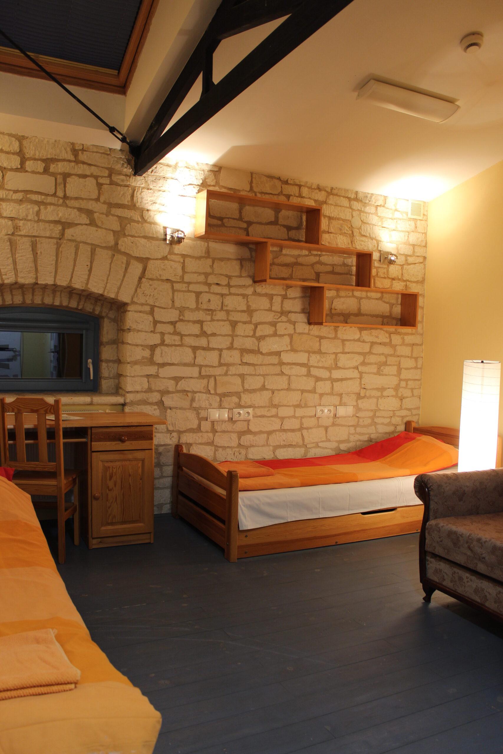 Zdjęcie pokoju, ściana z kamienia, łóżk, soda, biurko drewniane, drewniana półka zawieszona na ścianie z kamienia