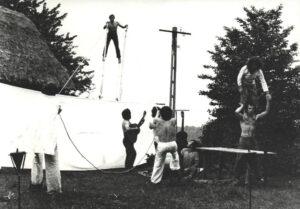 Na trawie, przed wiejską chałupą kryta strzechą, grupa ośmiu osób: siedmiu mężczyzn i kobieta. Przed chałupą rozpięto szeroki pas białego materiału. Dwóch mężczyzn trzyma liny stabilizujące trzeciego mężczyznę, który stoi za pasem materiału na wysokich szczudłach. Trzej inni przyglądają się temu; jeden z nich siedzi na ziemi, inny stoi i gra na gitarze. Z prawej strony, obok drewnianego stołu, kobieta w spódnicy i białej bluzce stoi na ramionach asekurującego ją mężczyzny w ciemnych spodniach.