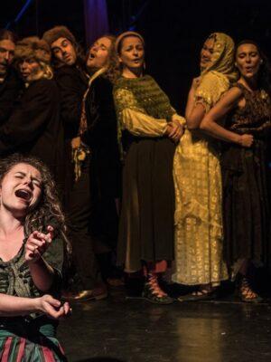 Ekspresyjna fotografia przedstawia młodą kobietę, która klęczy na czarnej scenie i śpiewa. Za nią, z tyłu, rząd dziesięciu nieco rozmazanych postaci, mężczyzn i kobiet, w kostiumach nawiązujących do estetyki ludowej. Wszyscy śpiewają i przyglądają się kobiecie na pierwszym planie.