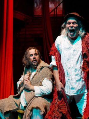 Fotografia przedstawia dwóch mężczyzn na ciemnym tle prowadzących do góry schodów i zwisających z sufitu czerwonych zasłon. Mężczyzna po lewej stronie, z brodą i półdługimi włosami, siedzi i spogląda na stojącego po prawej stronie starszego, siwowłosego mężczyznę, który głośno krzyczy.