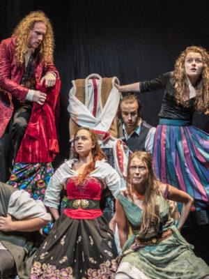 Na czarnym tle sześć osób ekspresyjnie upozowanych osób w dwóch rzędach, trzech mężczyzn i trzy młode kobiety, w kostiumach stylizowanych na polskie stroje ludowe z początku dwudziestego wieku. W pierwszym rzędzie, u dołu, siedzi mężczyzna z brodą i w zielony kapeluszu oraz dwie młode kobiety w strojnych sukniach. Nad nimi, z tyłu, stojący na niewidocznym podwyższeniu, młody mężczyzna w czerwonym surducie i z długimi, kręconymi blond włosami, młody mężczyzna w kamizelce, z zaczesanymi do tyłu włosami i młoda, ciemnowłosa kobieta w spódnicy w kolorowe pasy. Z prawej strony kadru sięga ku niej ręka z dłonią trzymającą pędzel.