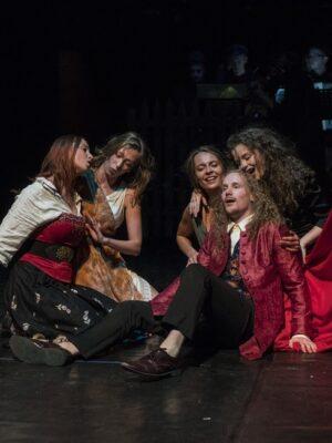 Ekspresyjna fotografia przedstawiająca pięć osób na ciemnej podłodze, pomiędzy dwiema zwieszającymi się z góry czerwonymi zasłonami. Po lewej stronie siedzą dwie młode kobiety; jedna z nich trzyma ręką zasłonę. Po prawej stronie siedzi młody mężczyzna z kręconymi, długimi włosami, ubrany w czerwony surdut i czarne spodnie. Zza niego wyłaniają się kolejne dwie śpiewające, młode kobiety, trzymające ręce na jego ramionach,