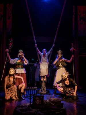 Symetryczna kompozycja obejmująca pięć osób na ciemnej scenie, oświetlonej tylko w centrum. Po lewej i prawej stronie zarysy schodów. Pośrodku, na podwieszonej u sufitu szarfie złożonej na wzór huśtawki, siedzi młoda kobieta w białek sukni. Po jej obu stronach stoją dwie kobiety w greckich maskach, trzymające rekwizyty przypominające pastorały. Przed nimi, na podłodze, kucają dwie kolejne młode kobiety, także zamaskowane.