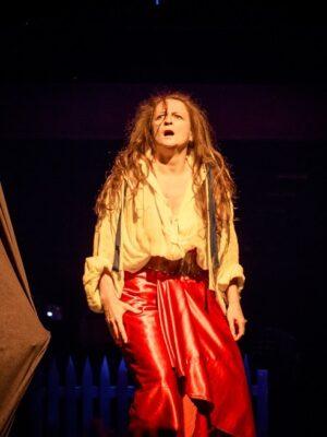 Na ciemnym tle długowłosa kobieta w białej koszuli i czerwonej spódnicy, spoglądające lekko w lewo. Ręce ma opuszczone wzdłuż ciała, usta otwarte. Po lewej i prawej stronie dwie pomarańczowo-brunatne kotary.
