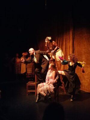 Scena teatralna na tle brązowo-pomarańczowej kurtyny, oświetlona punktowo jednym reflektorem, W centrum drewniana drabina. Z prawej strony stoi młoda kobieta w czarnej spódnicy, z nogą opartą o pierwszy szczebel. Na szczycie drabiny i u jej stóp siedzą kolejne dwie młode dziewczyny; wszystkie trzy wpatrują się w starszego, łysego mężczyznę w garniturze, który stoi oparty jedną ręką na drabinie, po lewej stronie, i wyciąga przed siebie rękę.