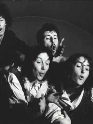 Czarno-biała fotografia przedstawiająca w ujęciu od piersi w górę dwóch śpiewających mężczyzn i dwie śpiewające młode kobiety na tle ściany i łuku sklepienia. Kobiety znajdują się bliżej obiektywu, mężczyźni za nimi. Wszyscy wyciągają ręce i patrzą w stronę prawego dolnego rogu kadru.
