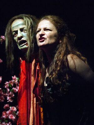 """Fotografia przedstawia ujętą od pasa w górę i nieco od boku, ubraną na czarno kobietę o długich włosach, która stoi tuż obok woskowej głowy o twarzy wykrzywionej w ekspresyjnym grymasie. Kobieta spogląda w prawo i w górę, a na jej twarz pada światło Po lewej stronie, nieco w tle, widać element dekoracji – gałęzie ukwieconego na różowo krzewu, pomiędzy którymi znajduje się prostokątna tabliczka z żółtym napisem """"Wiśnia Japońska Kwitnąca – CERASUS IAPONICA VIRDI""""."""