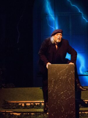 Fotografia przedstawia ciemną scenę, pośrodku której stoi prostokątny, czarny postument, na który wspina się okrakiem zdziwiony, starszy mężczyzna o długich, siwych włosach. Ma na sobie czarny płaszcz i ciemne buty, a na głowie przekrzywiony beret z antenką, również czarny. Za nim, w tle, wyświetla się animacja wyobrażająca błękitną błyskawicę. Po lewej stronie, wysoko, widać zawieszoną w ciemności i wydobytą plamą światła maskę o twarzy wykrzywionej w ekspresyjnym grymasie.