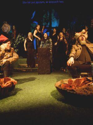 Fotografia przedstawia wyłożoną zieloną wykładzinę scenę teatralną. Na pierwszym planie, po lewej i prawej stronie, siedzą dwaj mężczyźni w strojach nawiązujących do mundurów żołnierskich i do ubiorów ludowych; siwy mężczyzna z lewej ma na głowie czerwoną, kościuszkowską rogatywkę, a mężczyzna z prawej, grubsza i z brodą, ma na głowie futrzaną czapę szlachecką. Mężczyzna z lewej odwraca się ku mężczyźnie z prawej, który trzyma dłonie na szeroko rozstawionych kolanach i śpiewa lub krzyczy. Przed każdym z nich stoi okrągła, szeroka misa wypełniona ziemią, z ustawionym pośrodku kolumnowym kaktusem w doniczce. Pomiędzy mężczyznami, na drugim planie, stoi czarny postument, przy którym stoi pięć śpiewających kobiet w ciemnych sukniach,