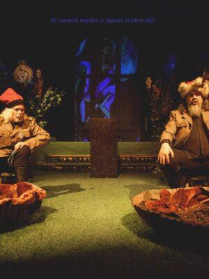 Fotografia przedstawia wyłożoną zieloną wykładzinę scenę teatralną. Na pierwszym planie, po lewej i prawej stronie, siedzą dwaj mężczyźni w strojach nawiązujących do mundurów żołnierskich i do ubiorów ludowych; siwy mężczyzna z lewej ma na głowie czerwoną, kościuszkowską rogatywkę, a mężczyzna z prawej, grubsza i z brodą, ma na głowie futrzaną czapę szlachecką. Przed każdym z nich stoi okrągła, szeroka misa wypełniona ziemią, z ustawionym pośrodku kolumnowym kaktusem w doniczce. Pomiędzy mężczyznami, na drugim planie, stoi czarny postument, a za nim, w ciemności, widnieją zarysy okna z niebieskim witrażem.