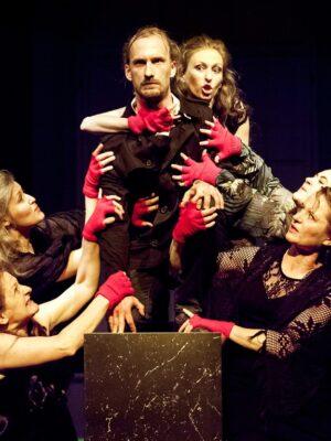 Fotografia przedstawia grupę pięciu kobiet i mężczyznę na czarnym tle. Pośrodku, na czarnym postumencie, kuca blondwłosy, młody mężczyzna z brodą. Po jego obu stronach stoją kobiety w ciemnych sukniach i w dłoniach obleczonych w czerwone rękawiczki bez palców, którymi dotykają tułowiu mężczyzny. Po lewej i prawej stronie, nieco z tyłu, znajdują się elementy dekoracji – niewysokie krzewy oraz dwie zawieszone wysoko maski o twarzach wykrzywionych w ekspresyjnych grymasach.
