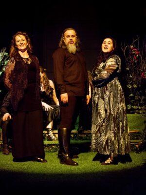 Fotografia przedstawia wyłożoną zieloną wykładziną scenę, z której szeroki snop światła wydobywa, na pierwszym planie, trzy stojące postaci – dwie młode kobiety i mężczyznę o długiej, siwiejącej brodzie. Kobieta po lewej uśmiecha się i jest ubrana w długą, czarną suknię. Kobieta po prawej ma czarne włosy, śpiewa i stoi lewym bokiem do obiektywu. Ubrana jest w długą suknię ozdobioną w całości wzorek podłużnych, zielonych liści. Mężczyzna stojący pośrodku, nieznacznie tylko wyższy, ma długie włosy, czarną koszulę i spodnie, oraz czarne buty o wysokich cholewach. Za nimi widać przesłonięte częściowo elementy scenografii – podwyższenie wyłożone zieloną wykładzinę oraz dwa krzewy, jeden zielony, a drugi zielony, upstrzony drobnymi, czerwonymi kwiatami.